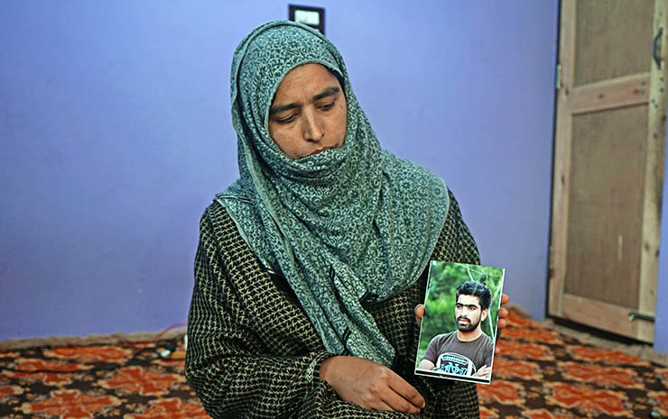 Tahira, Irfan Ahmad Dar's sister, holds his picture. Indian authorities have refused to return Irfan's body to the family for burial, and a committee investigating his death while in custody has yet to file a report of its findings.